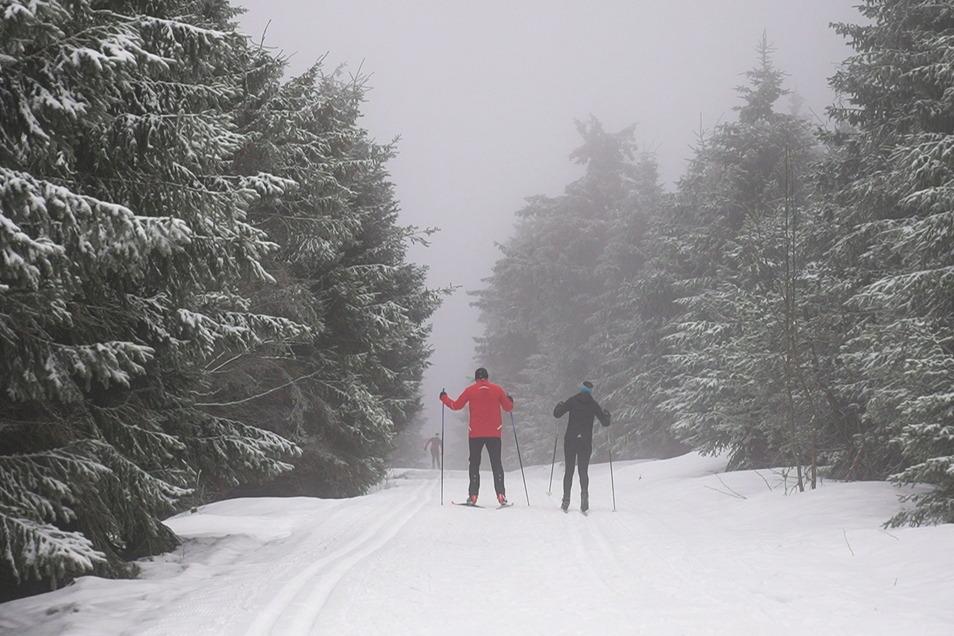 Skifahrer sind auf dem Fichtelberg im Erzgebirge unterwegs. Eine Kaltfront hat in der Nacht Schnee ins Erzgebirge gebracht.