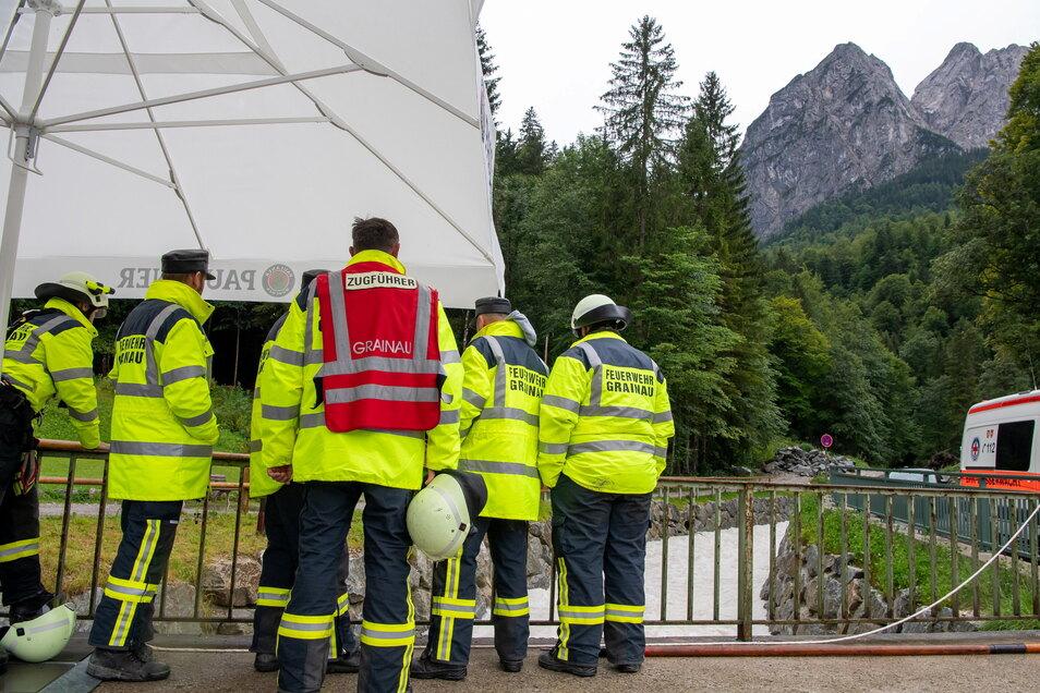 Mitglieder der Feuerwehr stehen nach einer Flutwelle in der Höllentalklamm bereit, um im Notfall Opfer aus dem Fluss Hammersbach zu bergen.