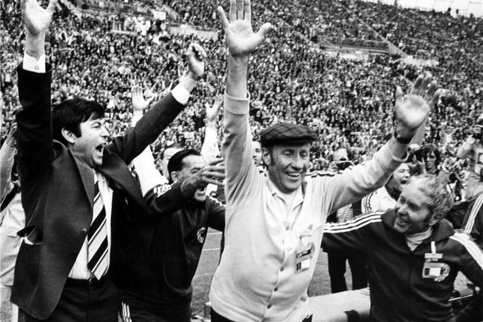 Flankiert von DFB-Sekretär Horst Schmidt (l) und Masseur Erich Deuser (r) reißt Fußball-Bundestrainer Helmut Schön (M) beim Schlusspfiff am 7. Juli 1974 im Münchner Olympiastadion jubelnd die Arme hoch. Die deutsche Nationalmannschaft gewinnt vor 80.000 Zuschauern das WM-Finale gegen die Niederlande mit 2:1 und wird zum zweitenmal Titelträger.