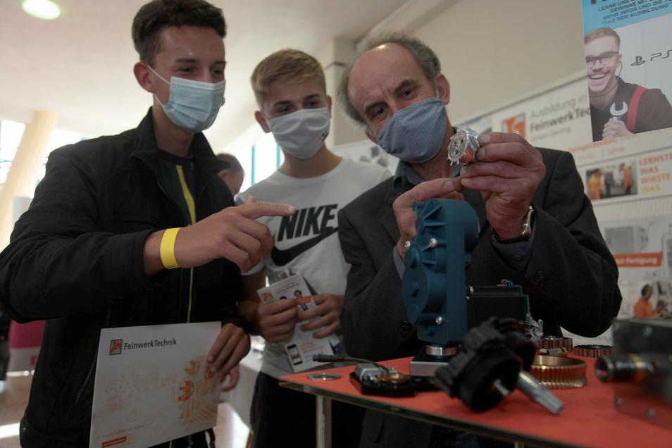 Ausbilder Jürgen Philipp (re.) von der Firma Feinwerktechnik in Geising erklärt den beiden Schülern Florian Berge und Anthony Tamme aus Pirna was der Betrieb produziert.