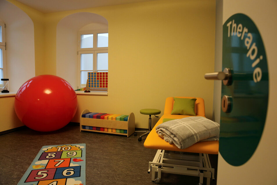 Hier arbeiten die Therapeuten mit Kindern und bringen Babys beim Krabbeln auf dem Riesenball in Bewegung.