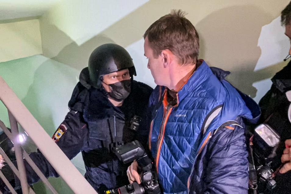 Ein Polizist steht vor Fotografen nahe der Moskauer Wohnung, wo Oleg Navalny, Bruder des inhaftierten Kremlgegners Alexej Nawalny lebt.