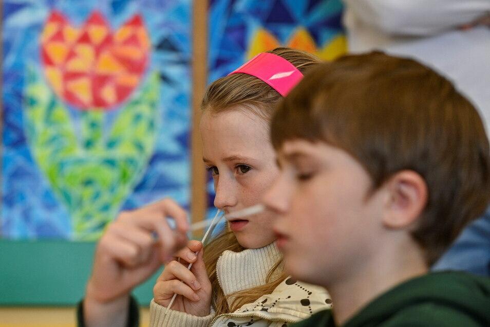 Zwei Schulkinder führen in einem Klassenraum einen Corona-Schnelltest durch.