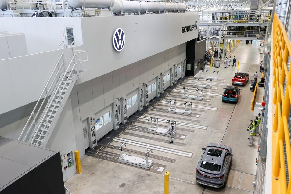 Die Elektrofahrzeuge vom Typ Audi Q4 e-tron, VW ID.3 und ID.4 fahren nach der Inbetriebnahme durch die Halle mit der neuen XL-Presse im Presswerk.