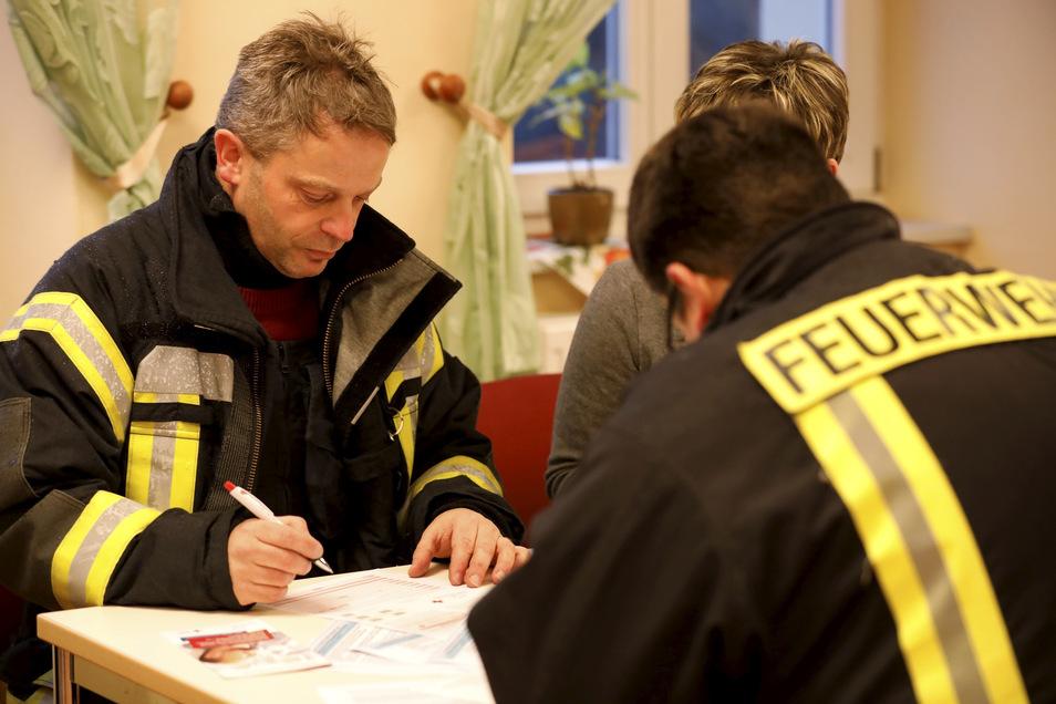 Thomas Schnuppe (links) und Thomas Birkner von der Kemnitzer Feuerwehr lassen füllen die Typisierungsbögen aus.