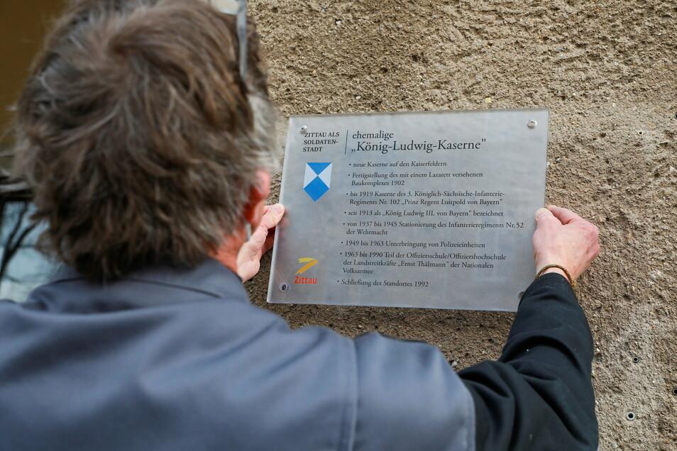 Die Plakette zählt die wichtigsten Daten der Standortgeschichte auf. Angebracht wird sie von Marius Kuettner von der Ostritzer Firma das-Werbung.