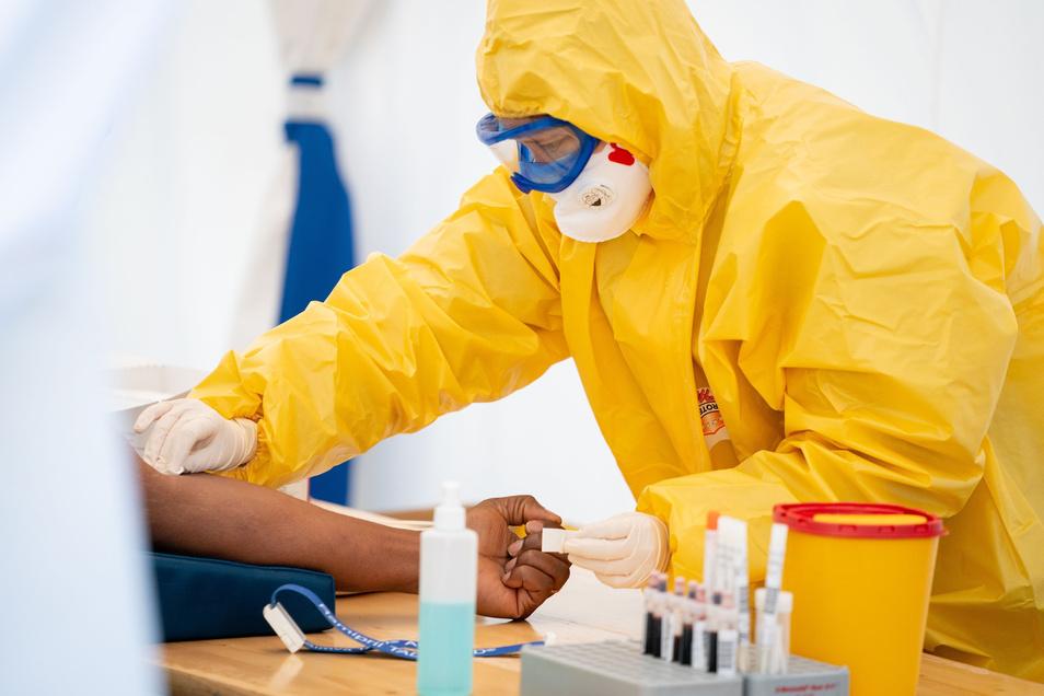 Eine Rettungssanitäterin entnimmt in Schutzkleidung in einem Zelt einem Patientin Blut.