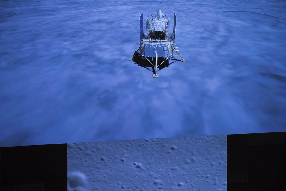 Ein Display zeigt die chinesische Raumsonde Chang'e 5 nach ihrer Landung auf dem Mond und darunter ein Foto mit der Oberfläche des Mondes, von einer Chang'e 5 Kamera aufgenommen.