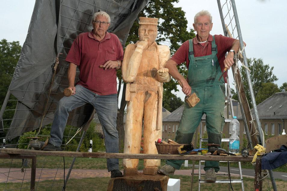 Helmut von Dach (links) und Hubert Harrand haben aus dem Stumpf einer Linde diesen Polizisten geschnitzt. Er steht am Verkehrsgarten vor der Kindertagesstätte in Ostrau.