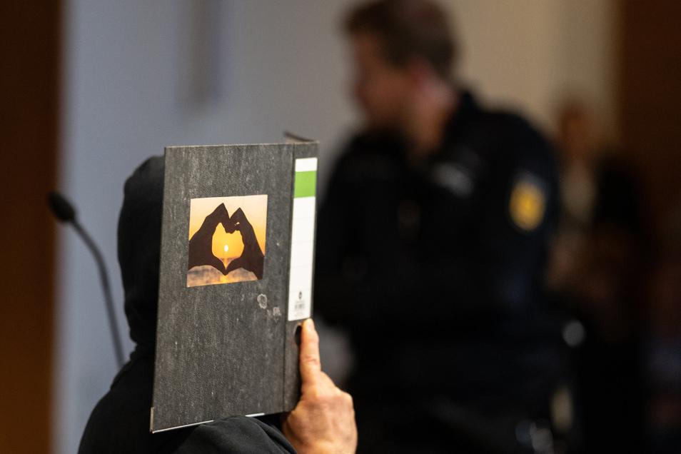 Der 58-jährige Angeklagte sitzt im Gerichtssaal im Landgericht und hält einen Aktenordner mit einem Herz aus zwei Händen vor sein Gesicht.