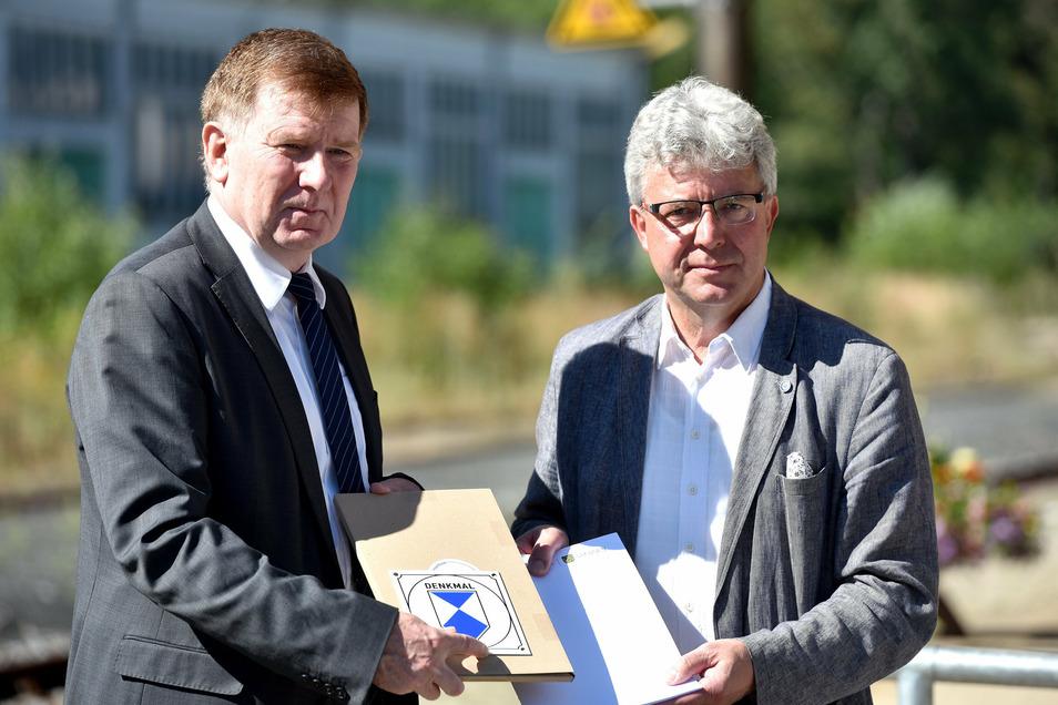 Frank Pfeil, Staatssekretär im Sächsischen Ministerium für Regionalentwicklung (l.) hat am Donnerstag die Förderbescheide für die Bahnhofssanierung an Großschönaus Bürgermeister Frank Peuker übergeben.