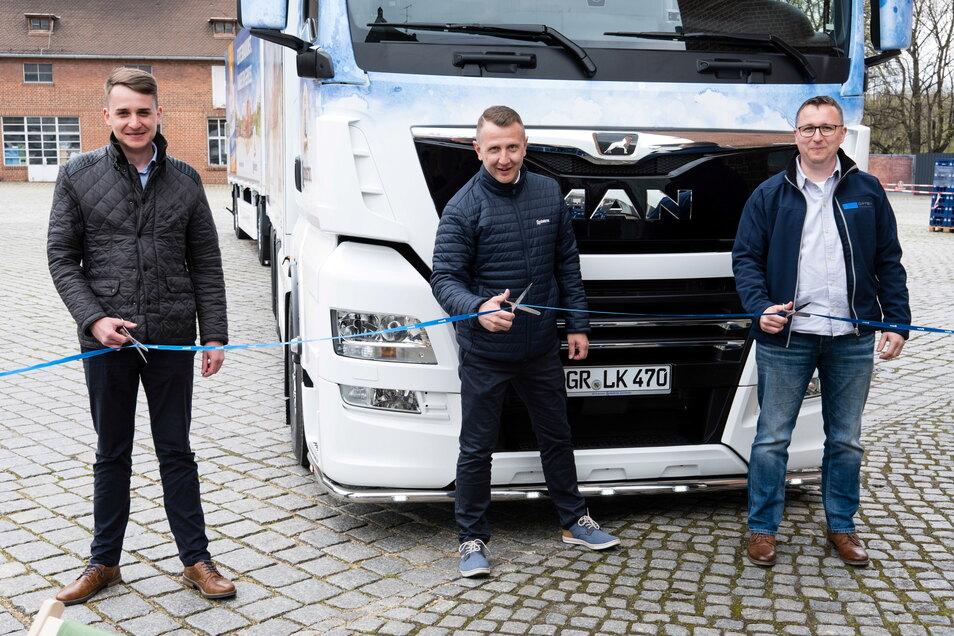 Paul Martin Vogt (Verkaufsbeauftragter von MAN), Markus Mücke (Fahrer von Landskron) und Nico Kretzschmar (Orten Fahrzeugbau) durchschneiden das Einweihungsband für den neuen Landskron-Lkw auf dem Brauereigelände in Görlitz.