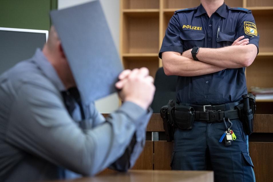 Der Angeklagte im Prozess um einen tödlichen Streit auf der Wiesn sitzt im Gerichtssaal und hält sich einen Ordner vor das Gesicht.