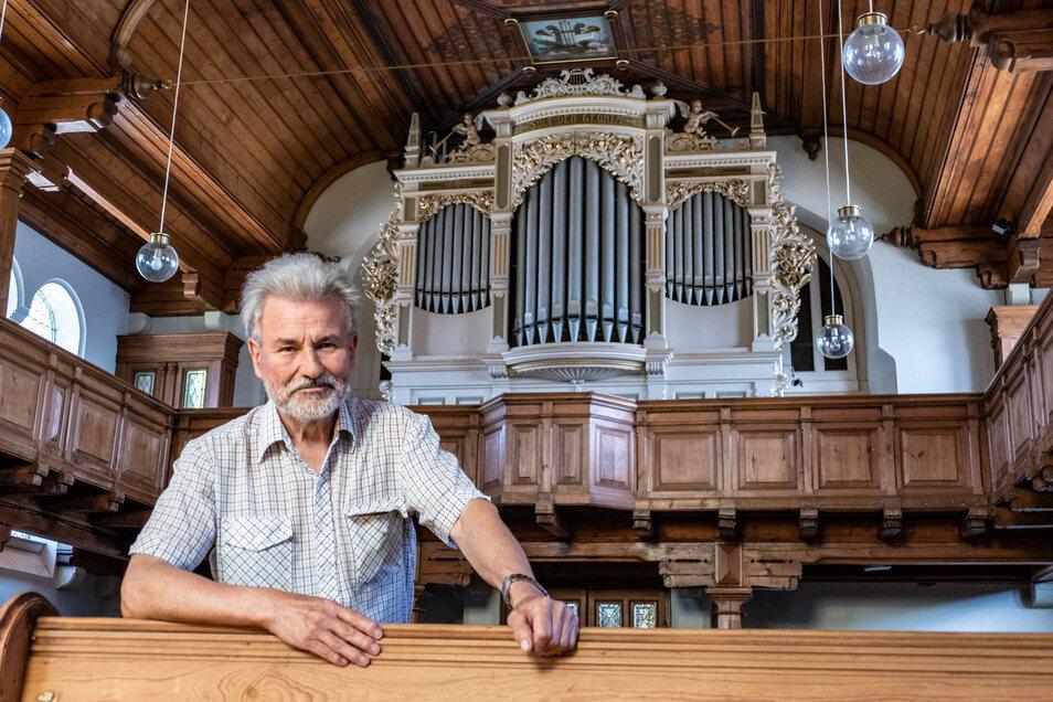 Pfarrer Reinhard Mehnert steht vor der Orgel in der Ostrauer Kirche. Er geht nach 36 Jahren in den Ruhestand.