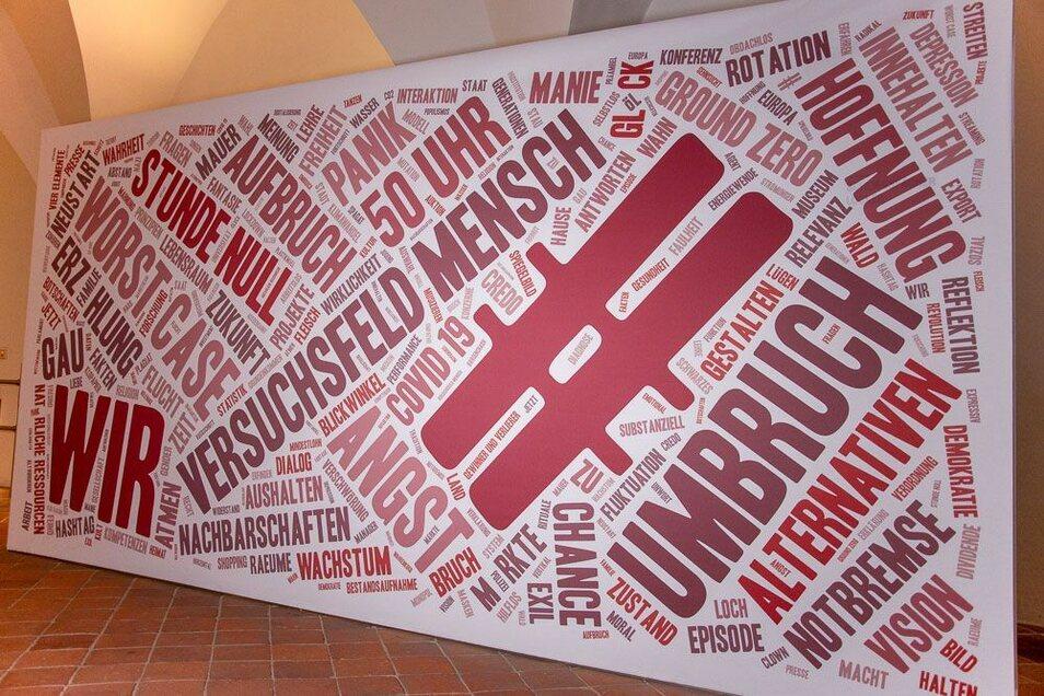 """Der Textildruck """"Versuchsfeld Mensch"""" eröffnet die Ausstellung mit zahlreichen Schlüsselbegriffen, die die in """"Emergency Break"""" dargestellte Ausnahmesituation versinnbildlichen."""