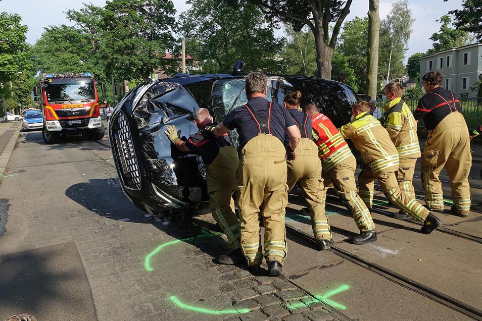 Die Berufsfeuerwehr ist im Einsatz, um den Audi wieder auf die richtige Seite zu bringen.