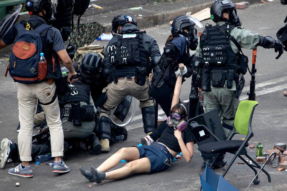 Bereitschaftspolizisten verhaften Demonstranten.
