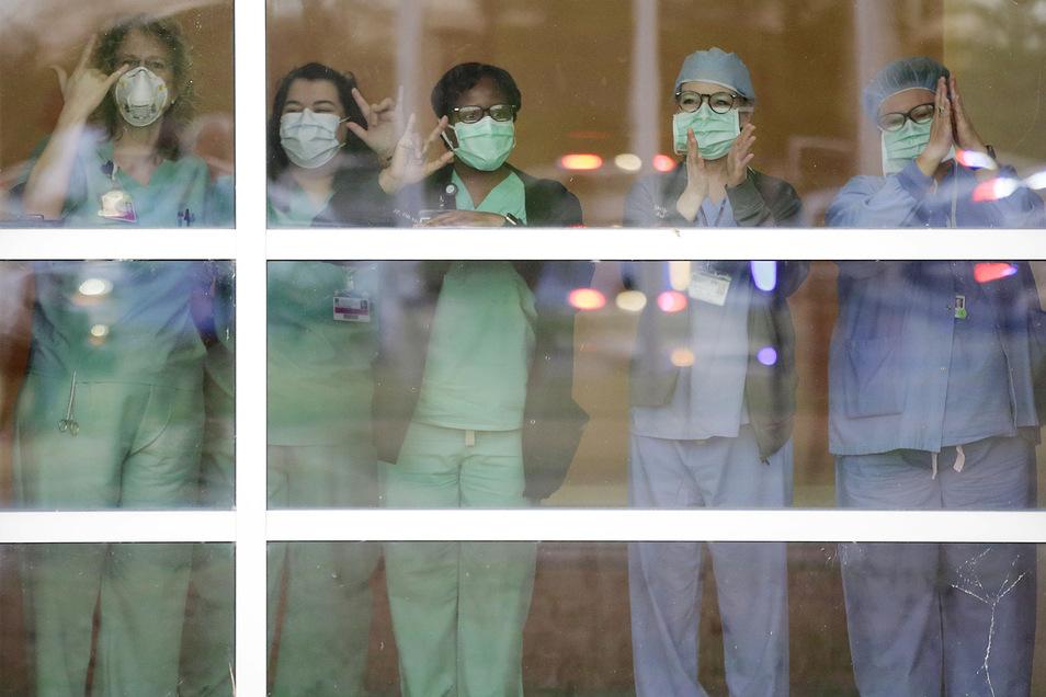 """USA, Tulsa: Mit Mundschutz stehen medizinische Mitarbeiter hinter einer Glasscheibe während der Veranstaltung """"Headlights for Hope"""" im Bailey Medical Center. Autofahrer schalteten auf dem Parkplatz vor dem Krankenhaus Scheinwerfer an und hupten, um den Är"""