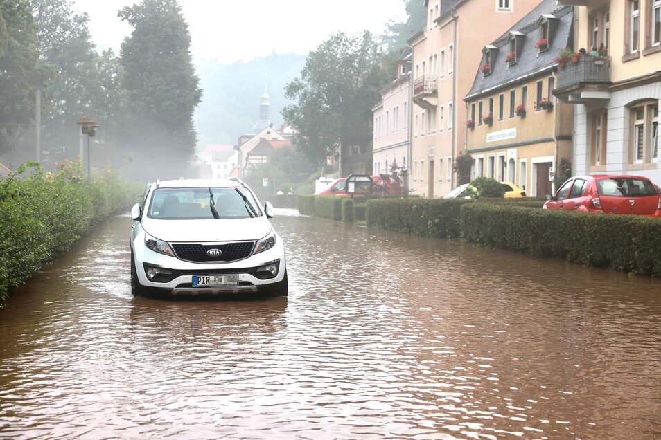 Wenn die Straße zum Fluss wird: Ein Auto auf der überschwemmten Kirnitzschtalstraße in in Bad Schandau.