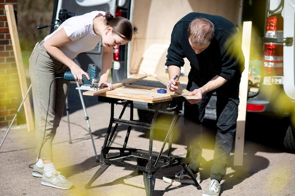Greta Thomas und Hannes Wehrmann sägen Holz vor ihrem Mercedes-Benz Sprinter zu, den das Paar in Eigenarbeit zu einem Campervan umbaut.