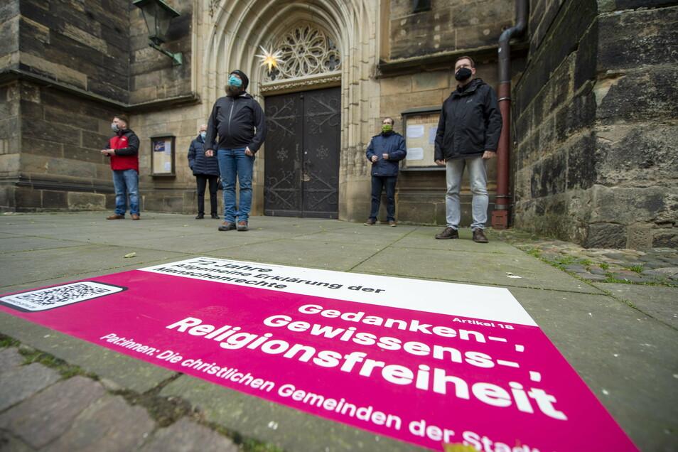 Menschenrechte-Aufkleber vor der Pirnaer Stadtkirche St. Marien: Hinweis auf die gemeinsamen, elementaren Werte.