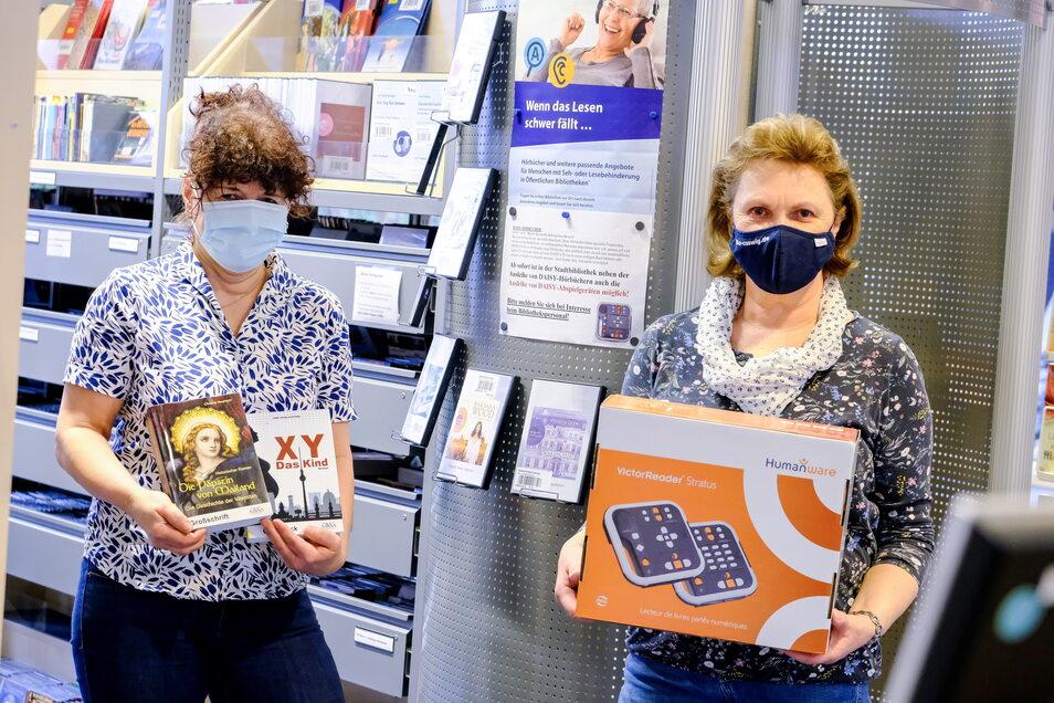 Michaele Niehoff (l.) und Inken Kretschmar von der Stadtbibliothek Coswig mit Büchern in Großdruck und einem Abspielgerät für Hörbücher. Diese Medien sind aus Mitteln der Alfred-Prescher-Stiftung angeschafft worden.
