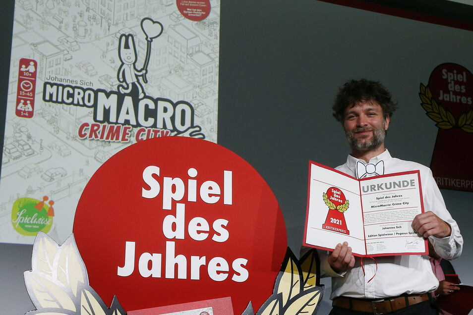 """Johannes Sich, Spieleautor, hält die Gewinnerurkunde zum Spiel des Jahres 2021 in den Händen. Sein Spiel, """"Micro Macro Crime City"""" wurde von einer Jury zum Spiel des Jahres gewählt."""