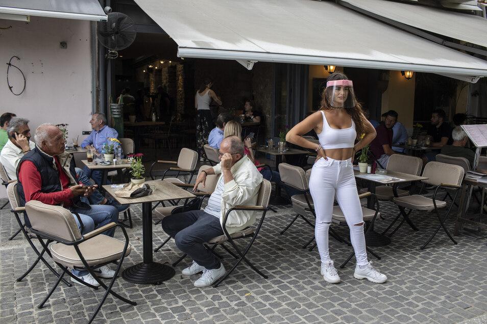 Eine Angestellte steht in Athen vor einem Restaurant. Der Tourismus macht in Griechenland und Italien 15 bis 20 Prozent der Wirtschaftsleistung aus.