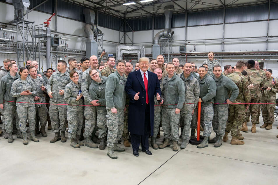 Donald Trump (M), Präsident der USA, lässt sich, während eines Zwischenstopps auf dem Stützpunkt der US-Luftwaffe in Ramstein im Dezember 2018, mit Militärangehörigen fotografieren.