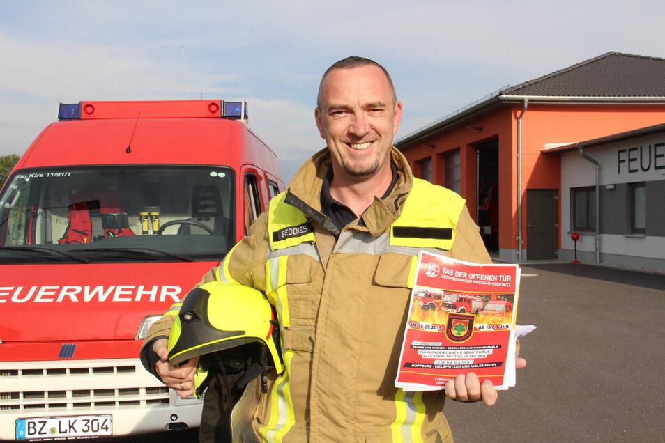 Ortswehrleiter René Beddies an der neuen Feuerwache von Rodewitz-Kirschau. Er zeigt das Plakat, das für den Tag der offenen Tür am Sonnabend wirbt.