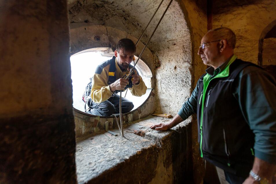 Gesichert mit zwei Seilen steigt der Uhrmacher aus dem Fenster im Dippser Kirchturm. Kirchner Andreas Kunath geht ihm zur Hand.