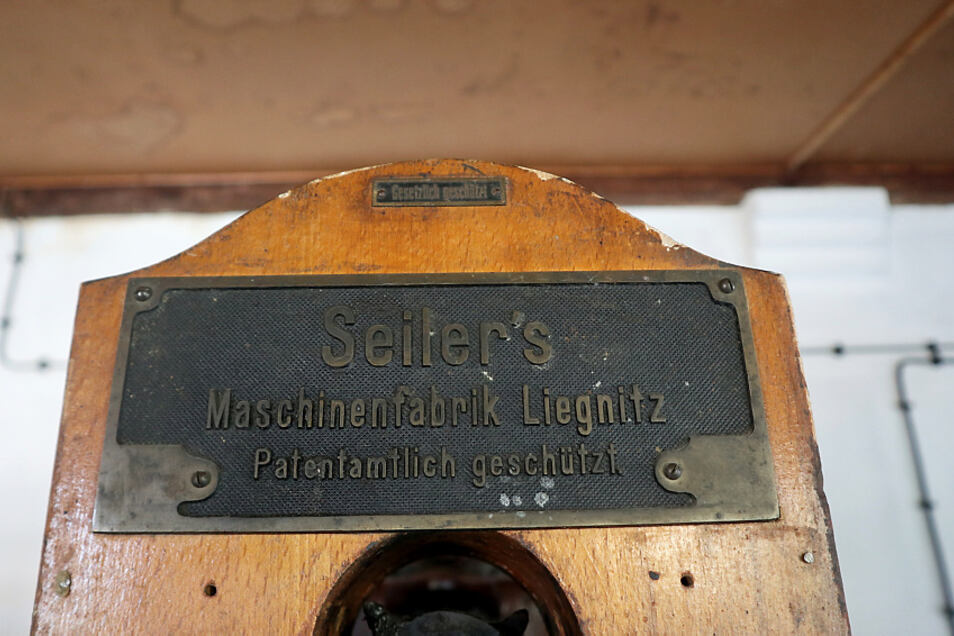 """""""Seiler's Maschinenfabrik Liegnitz. Patentamtlich geschützt"""" steht auf dem Firmenschild der Wäscherolle. Darunter ist der Bedienhebel. Ein Elektromotor mit Transmissionsriemen treibt die Wäscherolle an."""