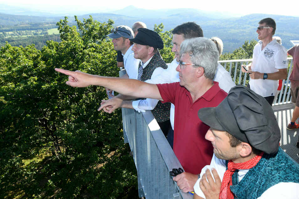 Vom neuen Aussichtsturm auf der Lausche reicht der Blick bis zum Jeschken. Großschönaus Bürgermeister Frank Peuker zeigt ihn dem Kreis-Hauptmann von Liberec Martin Puta, und Ministerpräsident Michael Kretschmer - in Oberlausitzer Tracht.