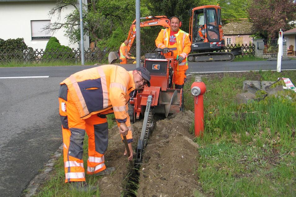 Mit der Fräse hat Dirk Winterlich auf dem Amselweg in Reichwalde 200 Meter Kabelgraben ausgehoben. Norbert Scheer (li.) musste mit der Schaufel nur noch Kleinigkeiten nacharbeiten.