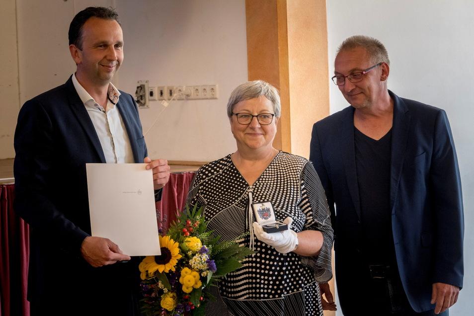 Seit mehr als 25 Jahren leitet Maritta Prätzel das Stadtmuseum Riesa; nun wurde sie mit der Ehrenmedaille ausgezeichnet. Links Oberbürgermeister Marco Müller (CDU), rechts der Vorsitzende des Museumsvereins Jürgen Gläsel.