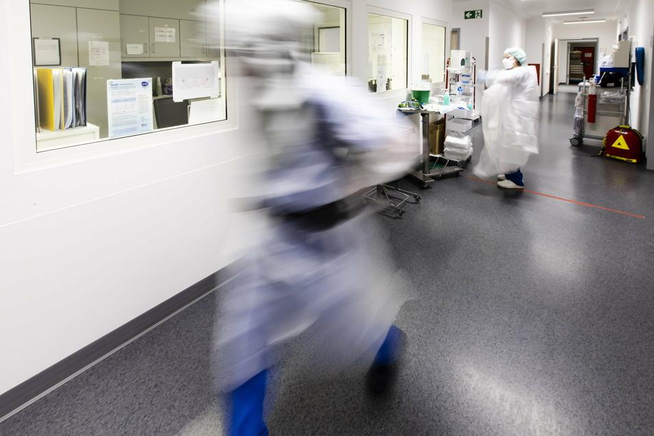 Ein Krankenpfleger läuft über einen Flur auf der Intensivstation am Universitätsklinikum Schleswig-Holstein. Die Zahl der Corona-Patienten auf deutschen Intensivstationen hat erfneut die Schwelle von 4.000 überschritten.