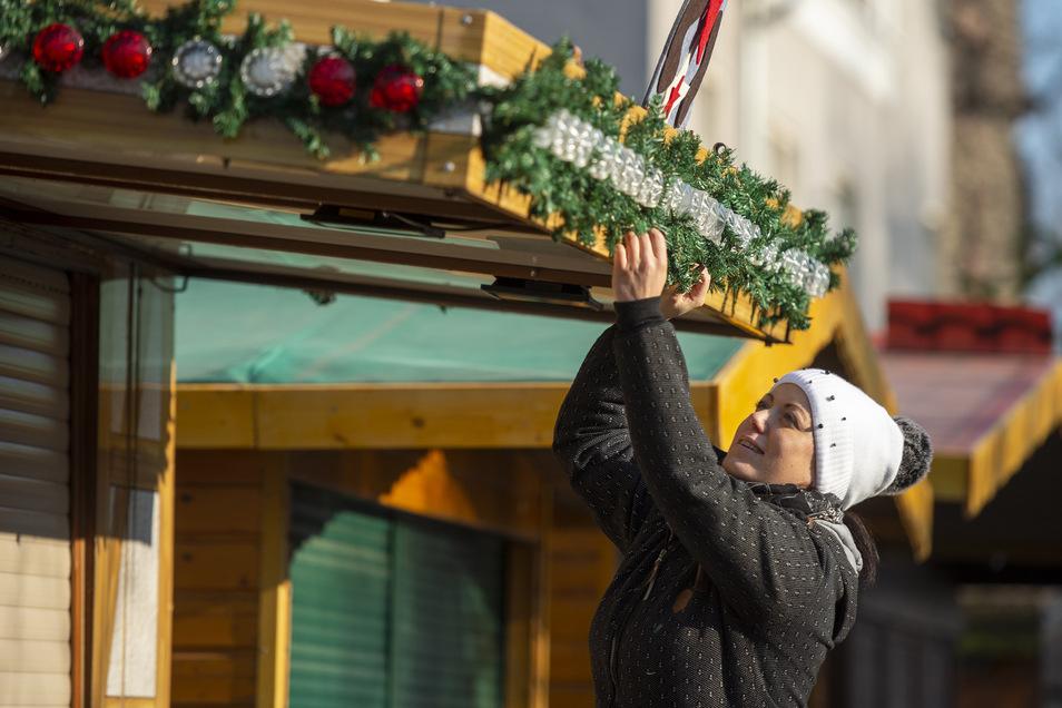Elisa Berndt schmückt eine der Buden auf dem Coswiger Weihnachtsmarkt. Am Freitag öffnet der Markt um 13 Uhr. In Weinböhla geht es eine Stunde später los.