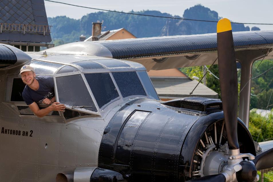 Erik Herbert im Cockpit seiner Antonov, dahinter der Blick auf die Schrammsteinkulisse.