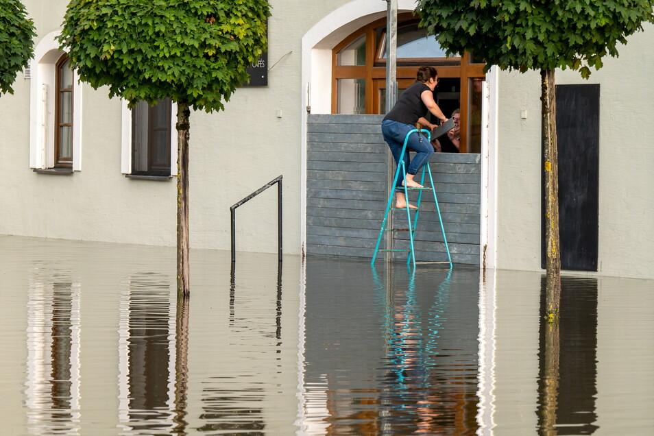 Passau: Zwei Personen dichten den Eingang eines Cafés mit einer speziellen Hochwassersperre ab, um das Gebäude vor dem Wasser der Donau zu schützen.