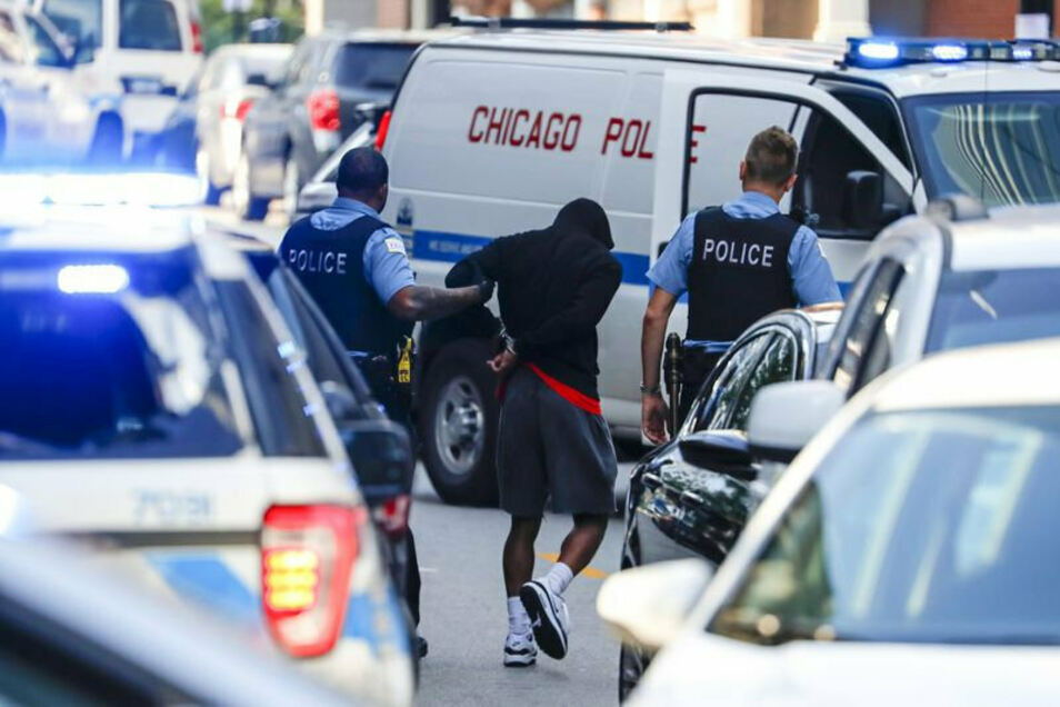 Polizeibeamte halten einen Mann auf der Straße in Chicago fest und führen ihn ab.