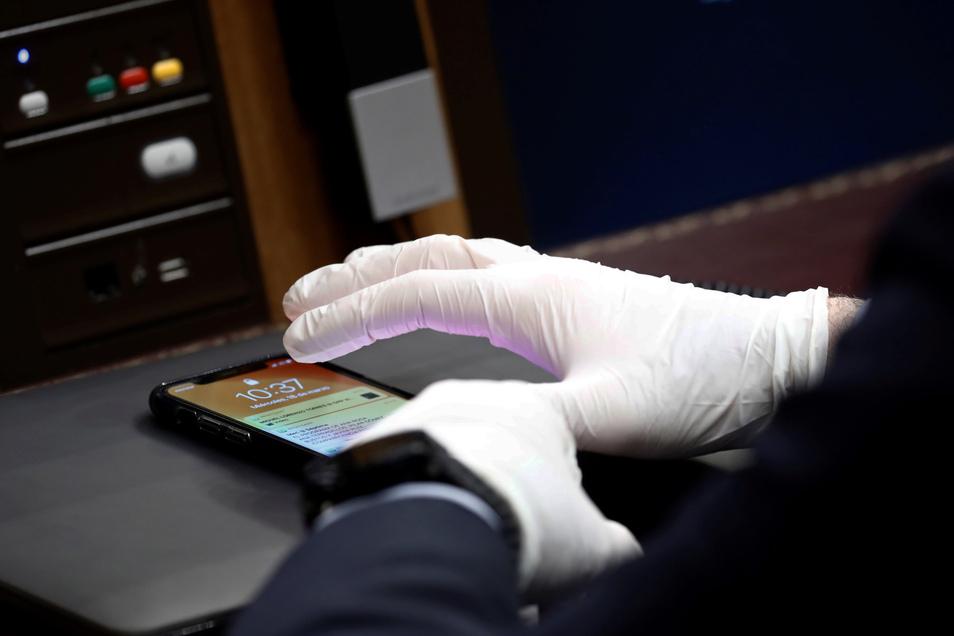 Ein Mann mit Einweghandschuhen benutzt sein Smartphone.