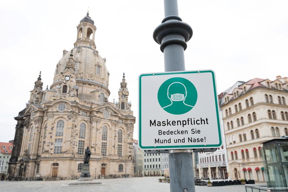 Ein Hinweisschild auf die Maskenpflicht hängt auf dem Neumarkt vor der Frauenkirche in Dresden.