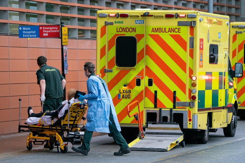 Sanitäter transportieren einen Patienten ins Royal London Krankenhaus. England befindet sich im dritten Lockdown zur Eindämmung der Corona-Pandemie.