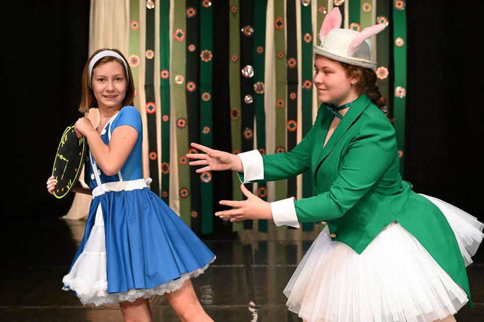 Alice (Enya, links), nimmt dem Kaninchen (Carolin) tänzerisch die Uhr weg.