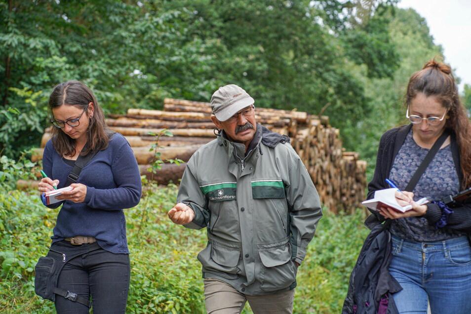 Bei einem Spaziergang auf dem Ringweg am Drohmberg erklärt Rüdiger Reitz den SZ-Reporterinnen Theresa Hellwig (r.) und Franziska Springer, wie die Waldrettung gelingen kann.
