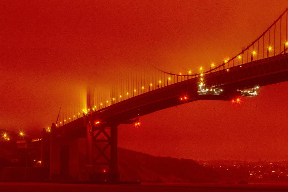 USA, San Francisco: Die Golden Gate Bridge ist in orangefarbenem Licht durch die anhaltenden Waldbrände zu sehen.