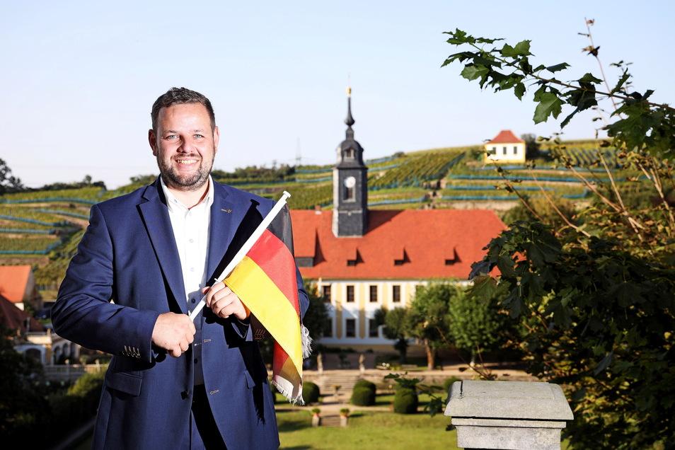Mit Fahne vor dem Schloss Seußlitz: Sebastian Fischer (39) möchte für die Meißner CDU in den Bundestag. Sein Thema ist auch der Patriotismus.
