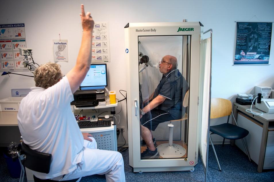 Reinhard Janzen sitzt zur Überprüfung seiner Lungenfunktion in einem Bodyplethysmographen