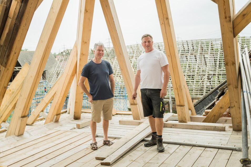 Henry de Jong und Zimmerer Mike Aust im sanierten Dachstuhl des Torhauses im Rittergut Tiefenau. Im Hintergrund: Das Scheunendach, dessen Sanierung nun folgen soll.