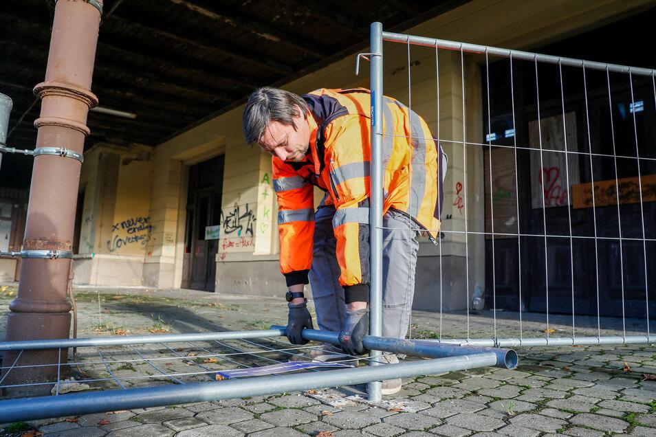 Ronny Däweritz von der DRE richtet einen umgestürzten Bauzaun am Bahnsteig in Seifhennersdorf wieder auf. Er ist umgetreten worden.